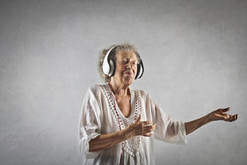 Ståenden av n åldrades kvinnan som lyssnar till musik royaltyfri foto
