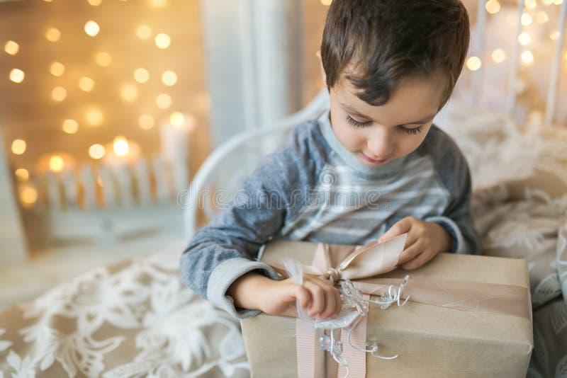 Ståenden av pojken öppnar lite en julklapp royaltyfri fotografi