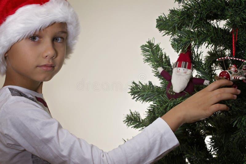Ståenden av pojken i jultomten cap att dekorera julgranen fotografering för bildbyråer