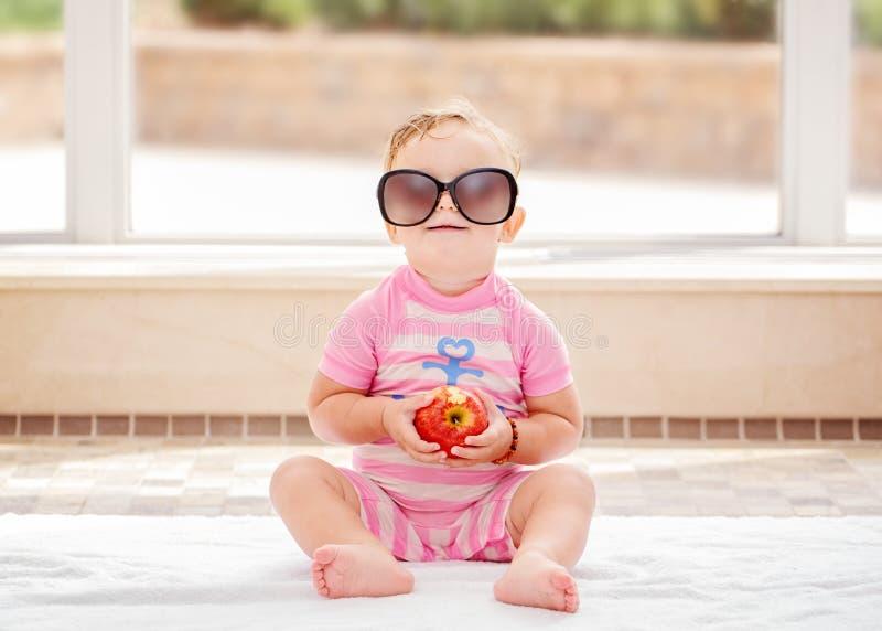 Ståenden av roligt gulligt vitt Caucasian le behandla som ett barn flickan som bär stor solglasögon som sitter på golv i simbassä arkivbilder