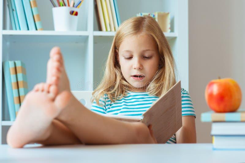 Ståenden av roligt litet koppla av för skolaflicka läser boken på royaltyfri foto