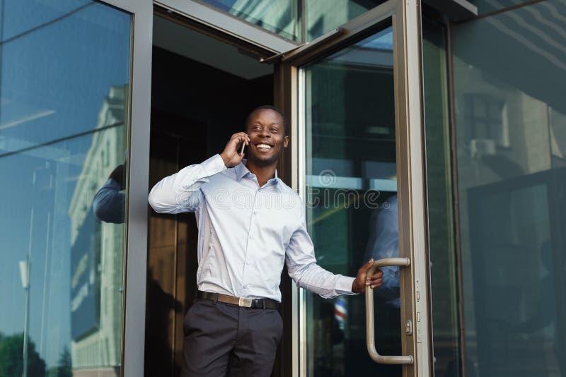 Ståenden av säkert barn svärtar affärsmannen som talar på mobiltelefonen royaltyfria bilder