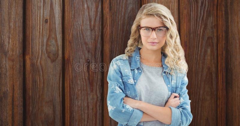Ståenden av säkra kvinnliga hipsteranseendearmar korsade mot träväggen arkivfoton