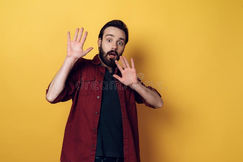 Ståenden av Shocked den skäggiga mannen håller upp händer arkivfoto