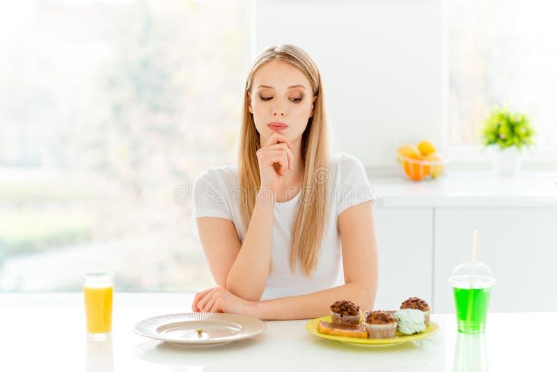 Ståenden av sinnat allvarligt eftertänksamt millennial avgör väljer grönsaken har bagerit för muffin för kvällsmållunchconfection royaltyfri fotografi