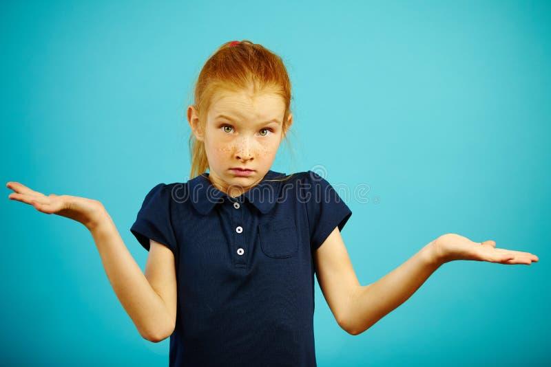 Ståenden av sju åriga flickalönelyfter rycker på axlarna och fördelar henne händer som uttrycker denna okunnighet eller förvirrin royaltyfria foton