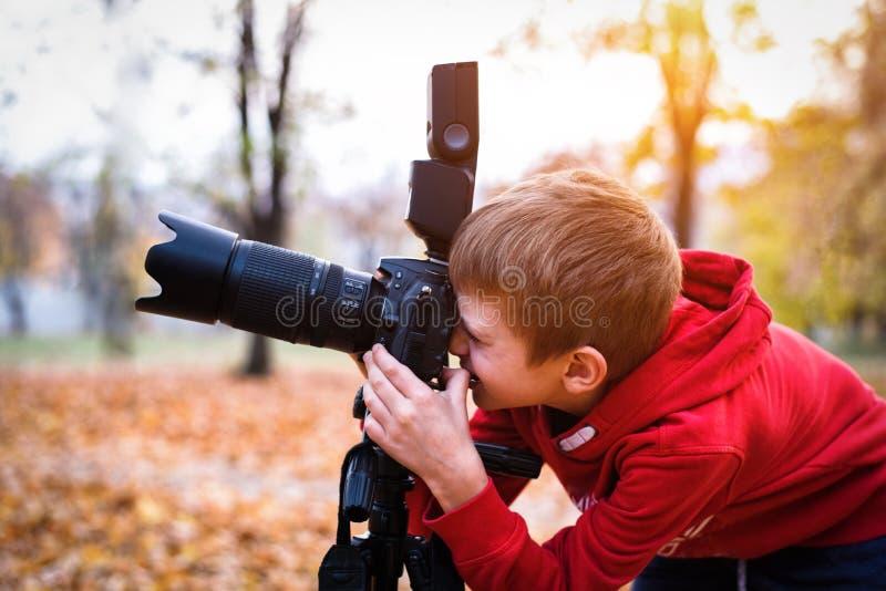 Ståenden av skolpojken tar bilder på en SLR kamera H?sten parkerar royaltyfri fotografi