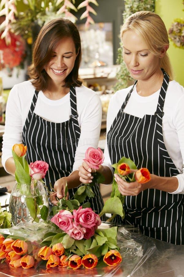 Ståenden av två försäljningsassistenter i blomsterhandlare shoppar arkivbild