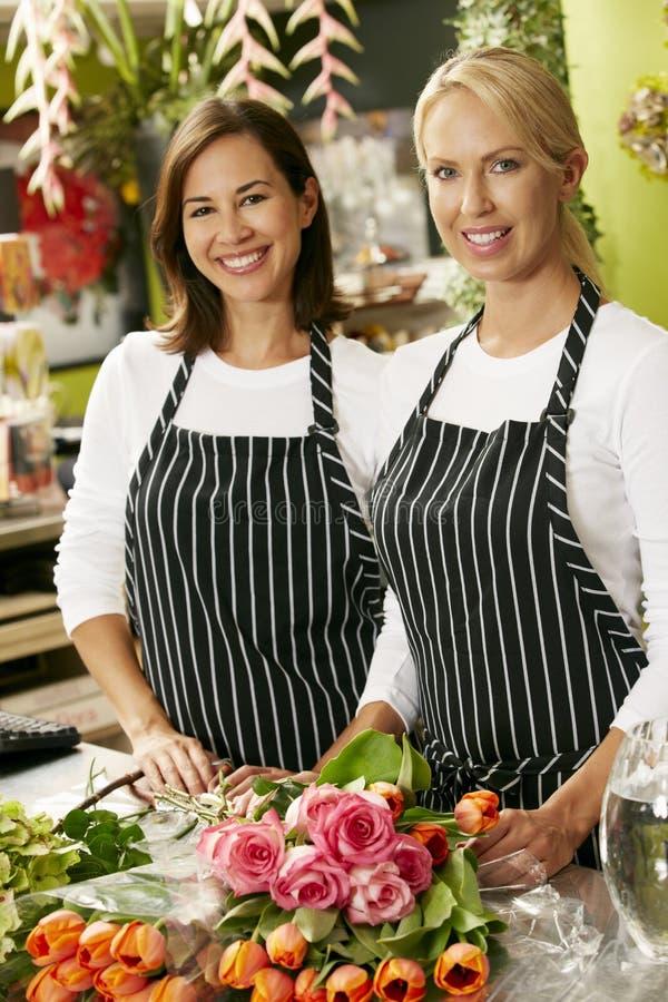 Ståenden av två försäljningsassistenter i blomsterhandlare shoppar royaltyfria foton