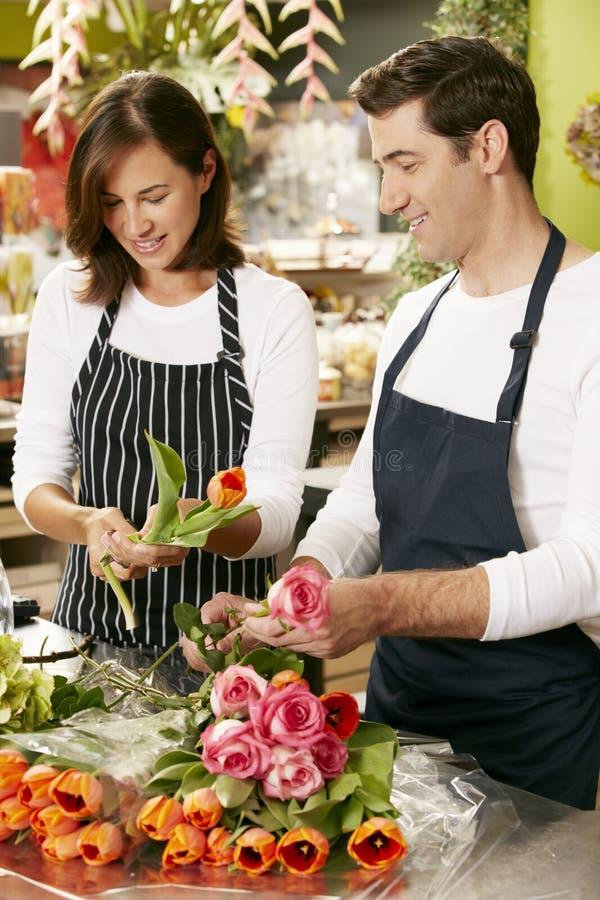 Ståenden av två försäljningsassistenter i blomsterhandlare shoppar fotografering för bildbyråer