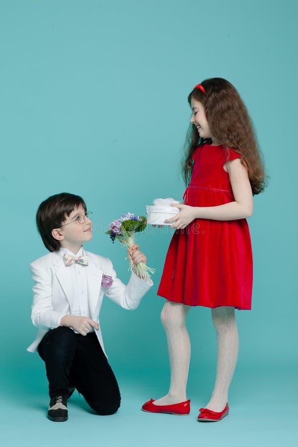 Ståenden av två förtjusande pojke och flicka, i den vita dräkten och röda klänningen som poserar i romantiskt, poserar på en blå  arkivbild