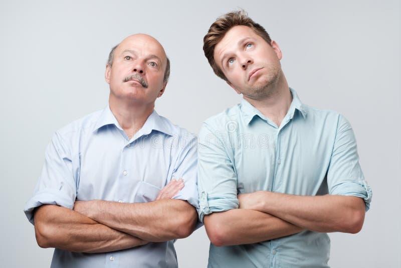 Ståenden av två män med borrat matat upp uttryckt, blickar misshog upp, tröttas för att förklara deras fruar var de var arkivbilder