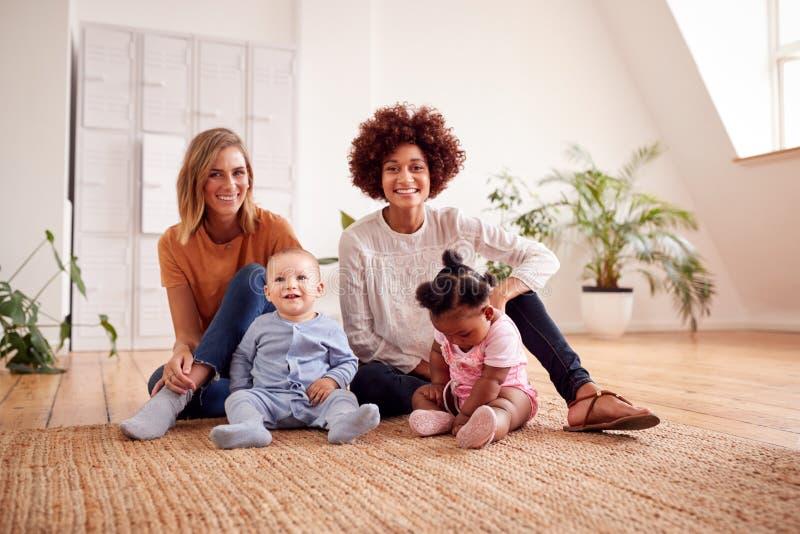 Ståenden av två mödrar som möter för lekdatum med, behandla som ett barn hemma i vindlägenhet royaltyfria foton