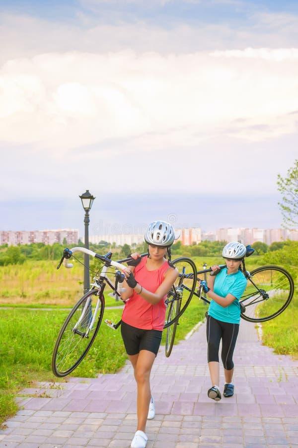 Ståenden av unga Caucasian idrottskvinnor utarbetar med cykelOu arkivfoton
