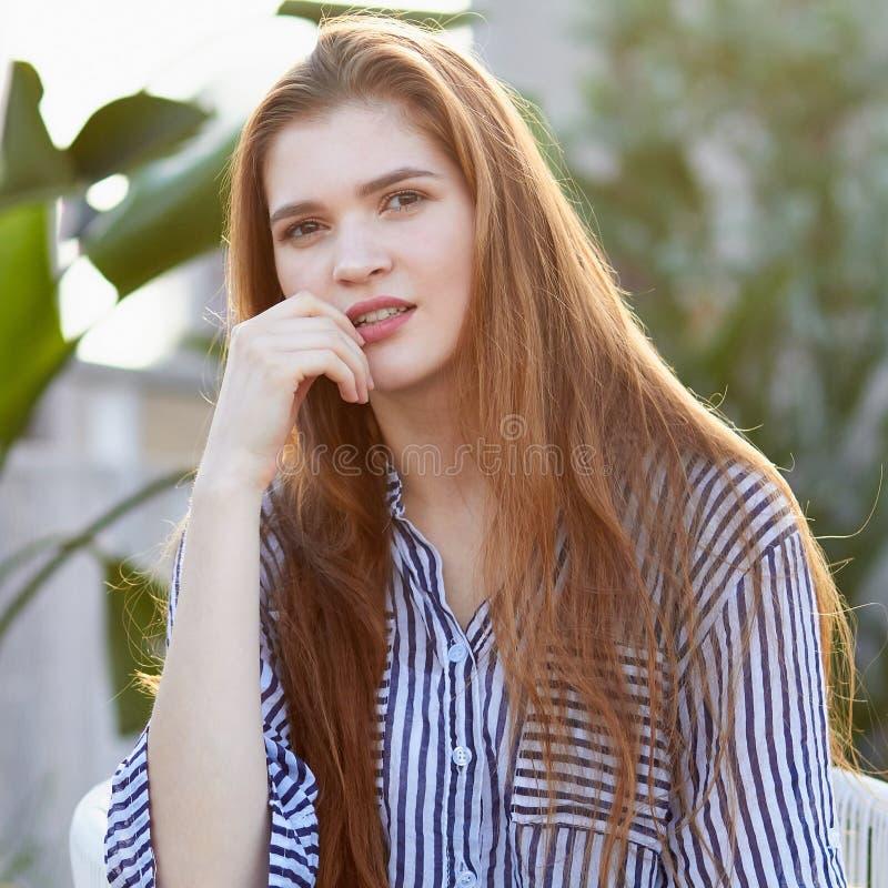 Ståenden av unga flickan sitter i den vita fåtöljen mot suddig balckground arkivfoto