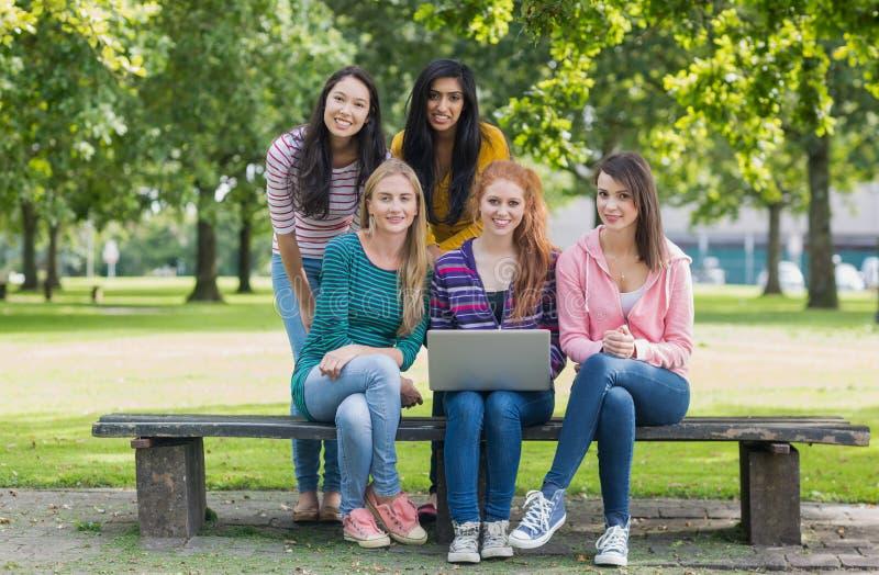 Ståenden av unga högskolaflickor med bärbara datorn parkerar in royaltyfri fotografi