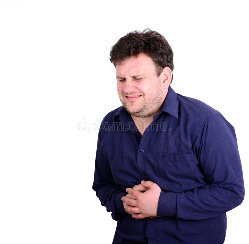 Ståenden av ungt affärsmanlidande från magen smärtar isolat arkivfoton