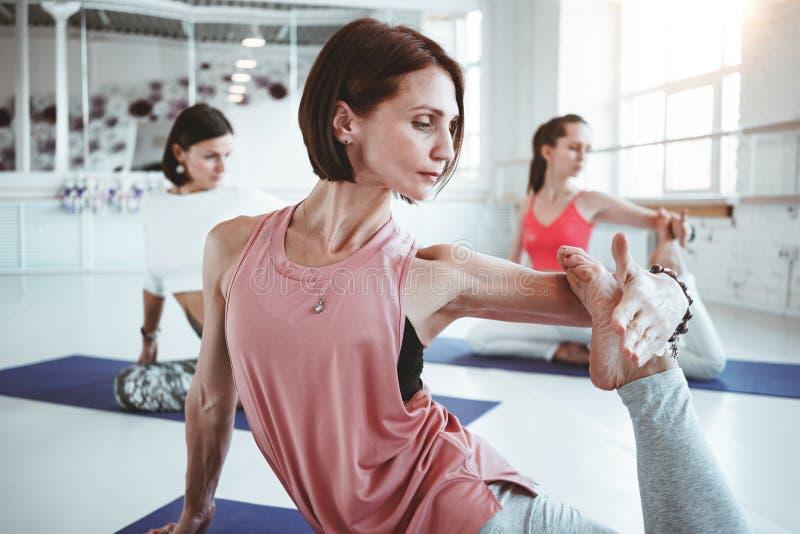 Ståenden av utbildande yoga för den starka färdiga kvinnan poserar på kondition som är matt samman med grupp människor på bakgrun arkivfoto