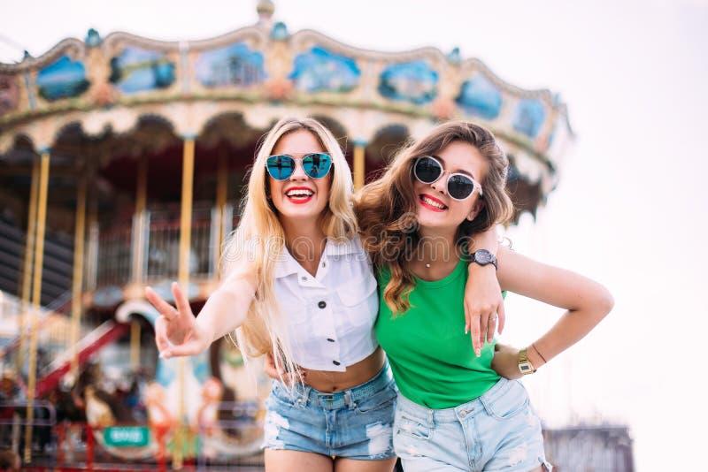 Ståenden för Closeupmodelivsstilen av två nätta bästa vänflickor, bärande blom- hattar för ljus byltestil, avspeglade solglasögon arkivfoto