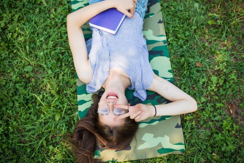 Ståenden för den bästa sikten av en nätt ung kvinna som kopplar av på ett gräs parkerar in arkivbild