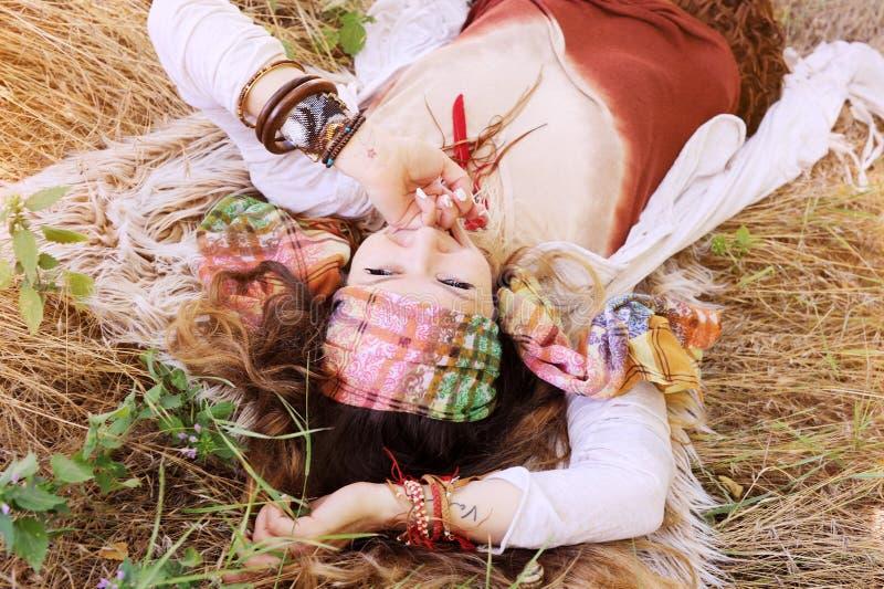 Ståenden för kvinnan för modebohostil, tycker om sommar som ligger på ett hö royaltyfri fotografi