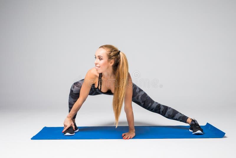 Ståenden för sidosikten av den härliga unga kvinnan som utarbetar mot den gråa väggen och att göra yoga eller pilates, övar på gr arkivbild