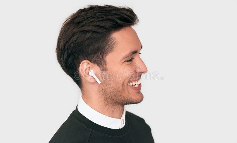 Ståenden för sidosikten av den stiliga unga mannen som ler och, har en appell på trådlösa hörlurar med en kollega som isoleras på arkivbild