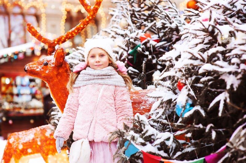 ståenden för vinterferie av den lyckliga barnflickan som går i stad, dekorerade för jul och nytt år royaltyfri foto