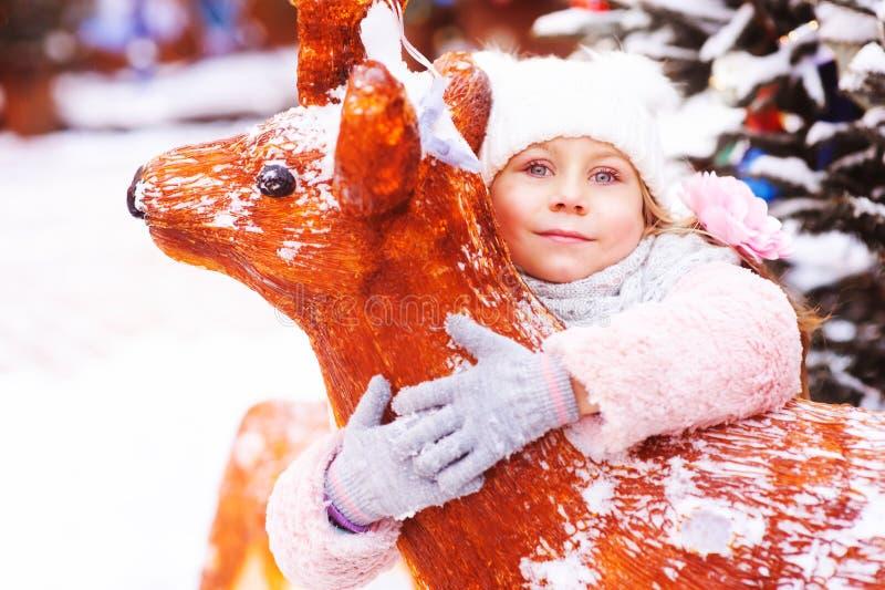 ståenden för vinterferie av den lyckliga barnflickan som går i stad, dekorerade för jul och nytt år arkivfoto