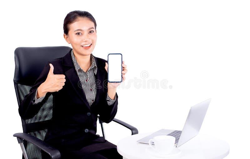 Ståenden isolerade sydostliga asiatiska affärskvinnan bär mörkt - den gråa dräkten ser kameran visar också hennes mobiltelefon på arkivbilder