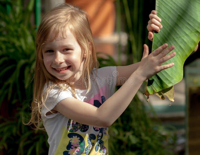 Ståenden lilla flickan av sju år, rymmer det stora bladet av palmträdet royaltyfria foton