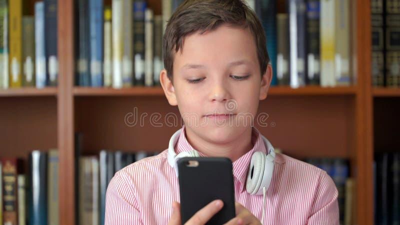 Ståenden sköt av den gulliga skolpojken med smartphoneanseende nära bokhyllan i arkivet arkivbilder