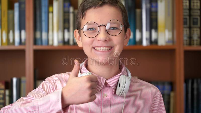 Ståenden sköt av det gulliga skolpojkeanseendet nära bokhyllan i arkivet och göratummen upp fotografering för bildbyråer