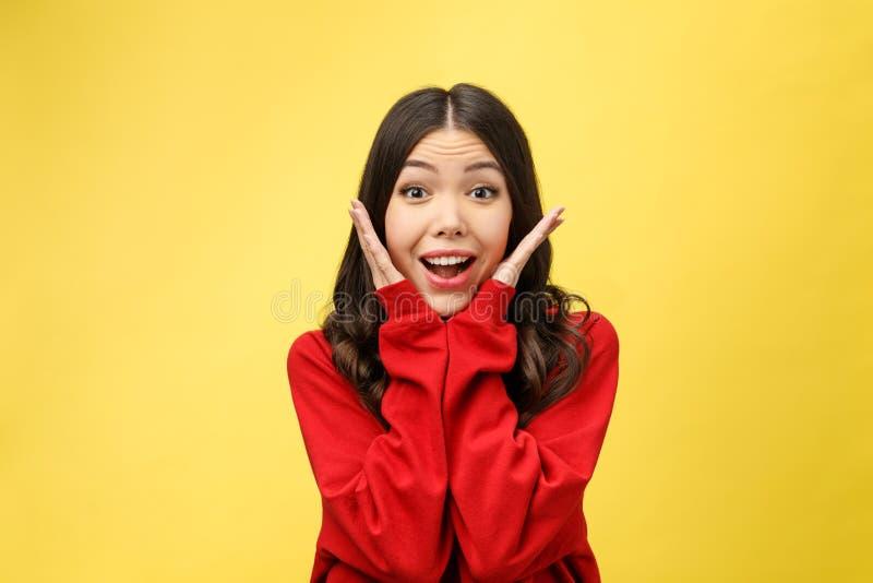 Ståenden som den lyckliga asiatiska flickan är förvånat henne, upphetsas gul bakgrundsstudio royaltyfria foton