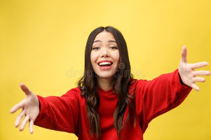 Ståenden som den lyckliga asiatiska flickan är förvånat henne, upphetsas gul bakgrundsstudio arkivfoton