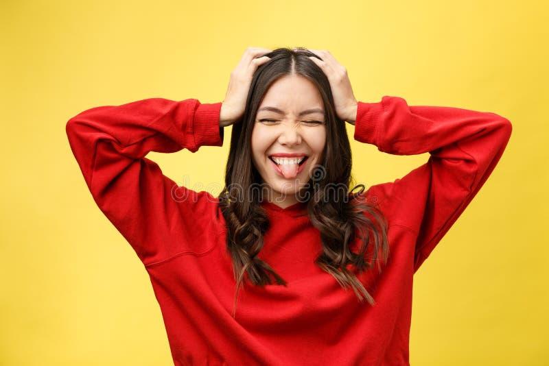 Ståenden som den lyckliga asiatiska flickan är förvånat henne, upphetsas gul bakgrundsstudio royaltyfri bild