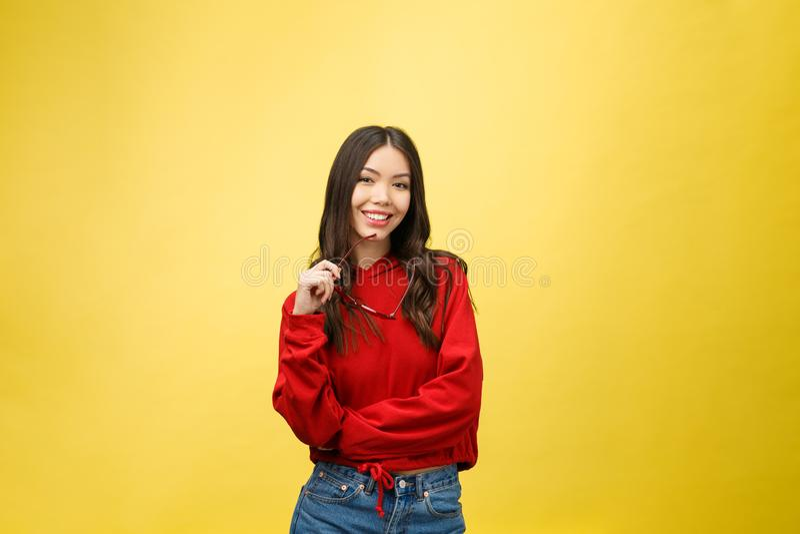 Ståenden som den lyckliga asiatiska flickan är förvånat henne, upphetsas gul bakgrundsstudio arkivbilder