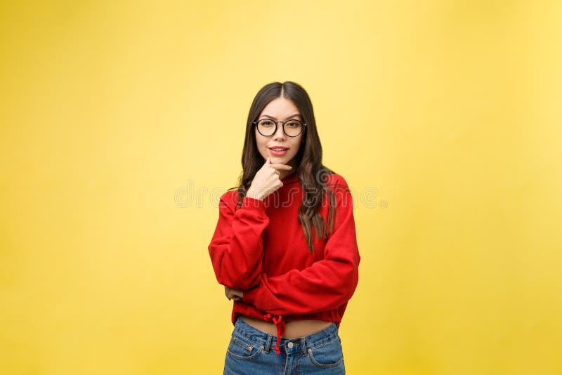 Ståenden som den lyckliga asiatiska flickan är förvånat henne, upphetsas gul bakgrundsstudio fotografering för bildbyråer