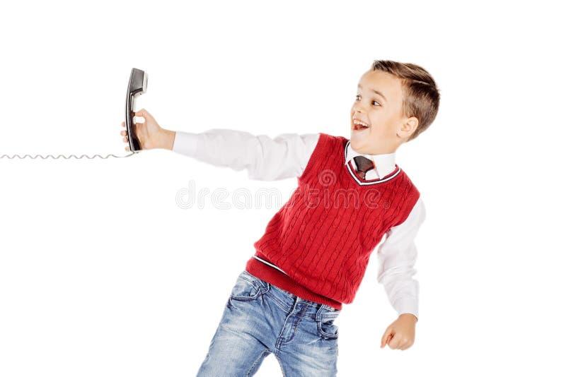 Ståendepojke som talar känslomässigt på den band telefonen på whit royaltyfri bild