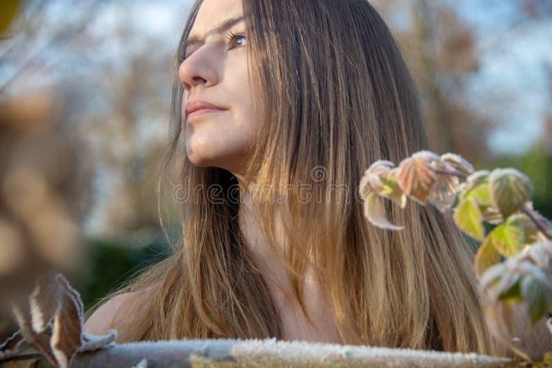 Ståendeprofil av en ung kvinna i vinter i trädgården på gjutjärnstaketet med frosthoarfrost fotografering för bildbyråer