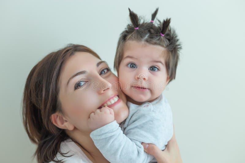 Ståendesikten av gulligt behandla som ett barn flickan och hennes mamma royaltyfri foto