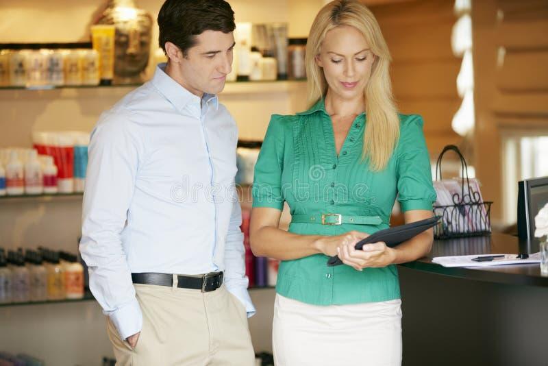 Ståendeskönhetsprodukten shoppar chefer som använder den Digital minnestavlan arkivfoton