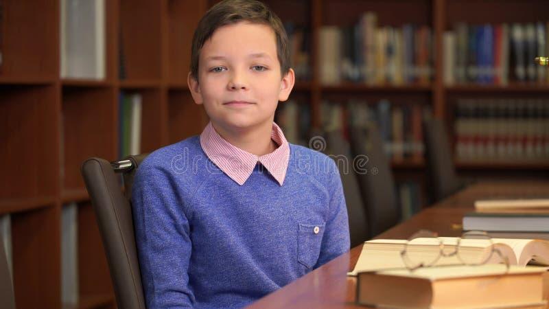 Ståendeskottet av den gulliga skolpojken sitter nära bokhyllan i arkivet royaltyfria foton
