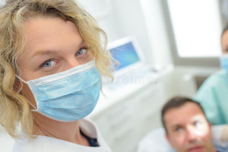 Ståendetandläkare i maskeringen som ser den tand- kliniken för kamera arkivfoto