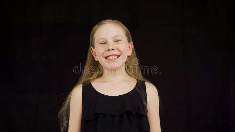 Ståendetonåringflicka som talar och trycker på långt blont hår på svart bakgrund arkivfoto