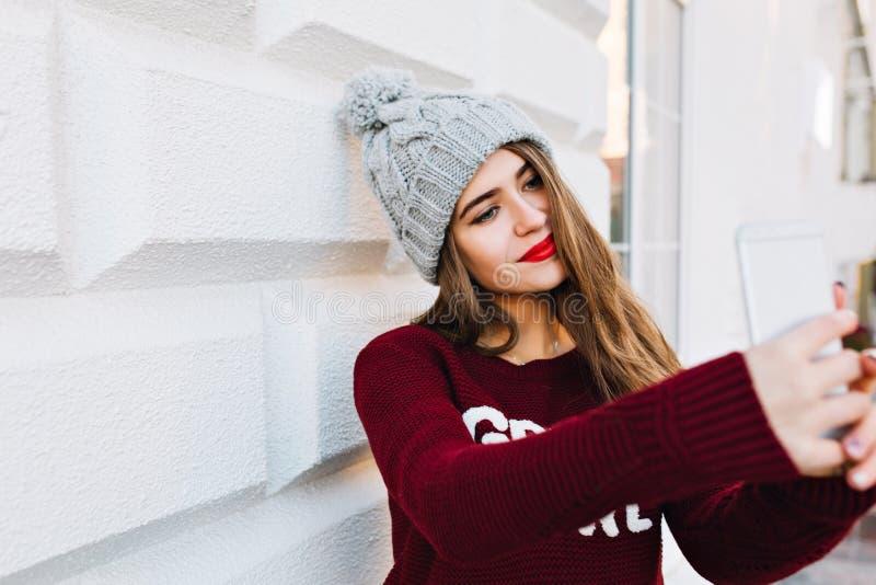Ståendeung flicka med långt hår som gör selfie på grå väggbakgrund Hon b?r den stack hatten och har r?da kanter royaltyfria bilder