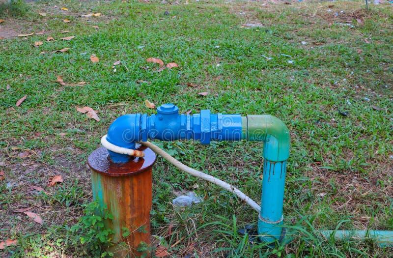 Stål för vattenventilrörmokeri har reparationsrör med att ändra av sammanfogade och målade blått på gräset royaltyfri foto