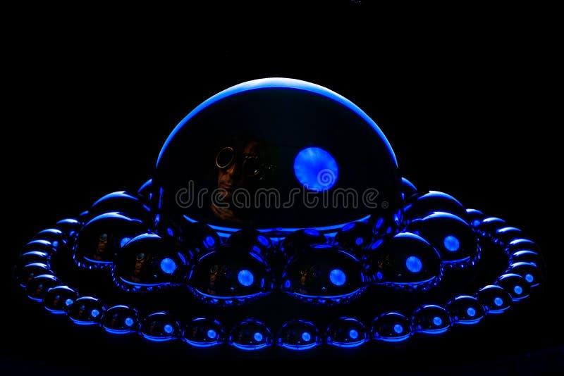 Stålbollar i omlopp runt om de i ett blått livligt hårt ljus En mycket subtil steampunkforskare reflekteras i det stort arkivbilder