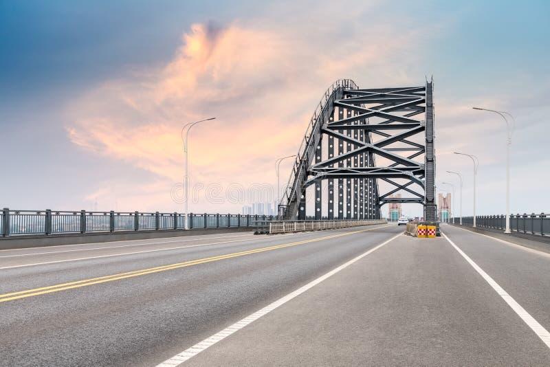 Stålbro och väg med skymninghimmel fotografering för bildbyråer
