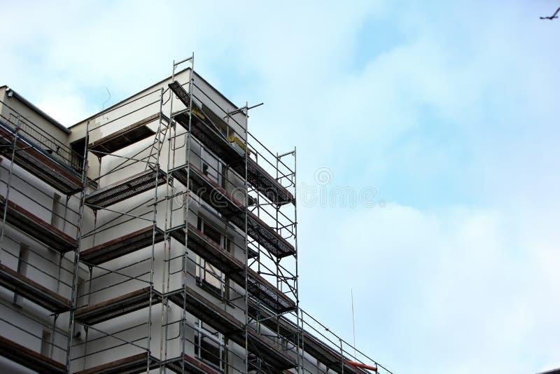 Stålmaterial till byggnadsställning som används för façaderenoveringarbeten royaltyfria bilder